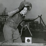 Official U.S. Navy Photograph. [Hazel Licuori raises her helmet and takes a breath before resuming her job as an oxyacetylyne burner], 1944. New-York Historical Society.